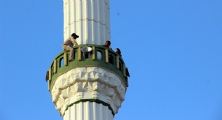 Sığınma evindeki eşi dönsün diye minareye çıktı