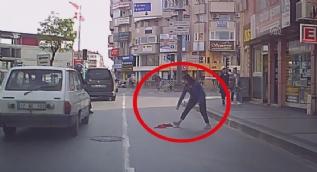 Yola düşen Türk bayrağını araçlar üstünden geçmesin diye aldı
